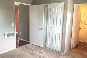 carpeted bedroom facing the tandem bathroom, white closet doors, and bedroom door