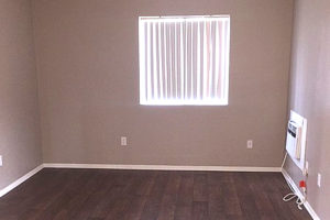 Bedroom with window, hardwood floors, neutral color walls and built in AC unit